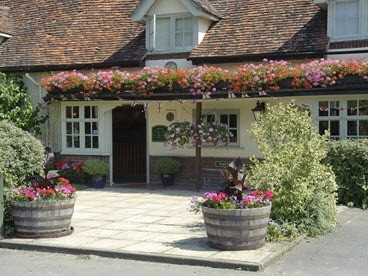 Hanging baskets and planters outside village pub in Tostock, Suffolk.